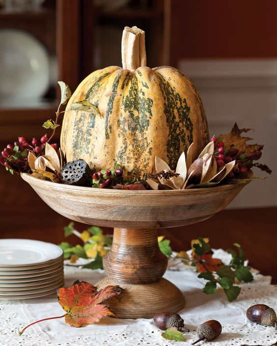 a pumpkin with dried blooms, berries, leaves and lotus on a wooden stand is a lovely rustic centerpiece to make