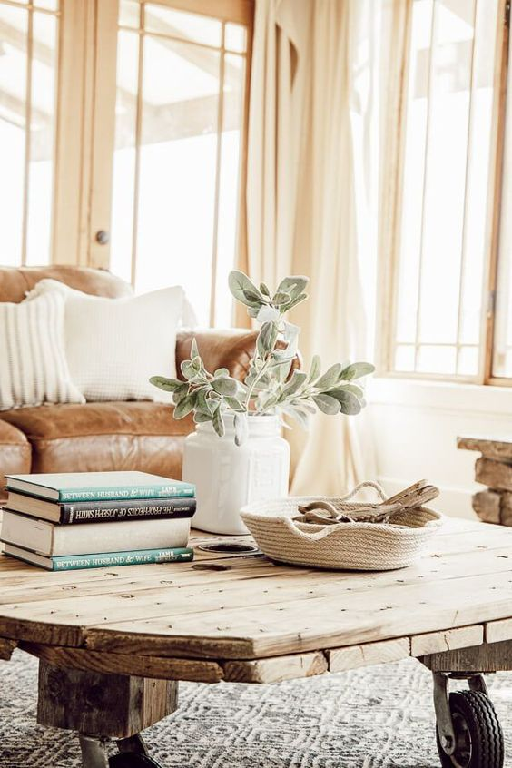 a reclaimed wood coffee table, a woven tray, a white vase with greenery and a stack of books