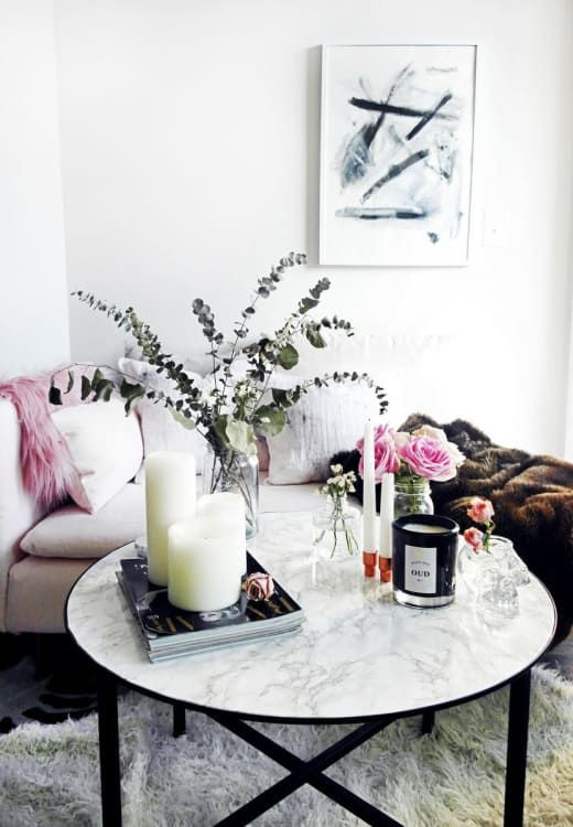 a refined arrangement of pillar candles, magazines, bright blooms in clear vases and eucalyptus in a clear vase