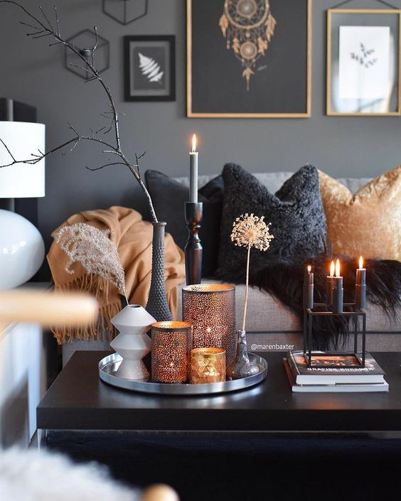 a refined coffee table arrangement with a modern candelabra with black candles, a trya with perforated candle holders and dried branches and herbs