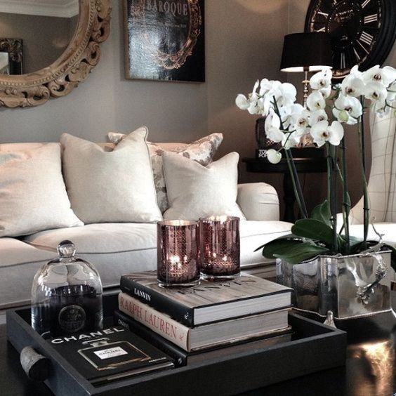 a refined coffee table arrangement with potted white orchids, a stack of books, a candle and a black tray