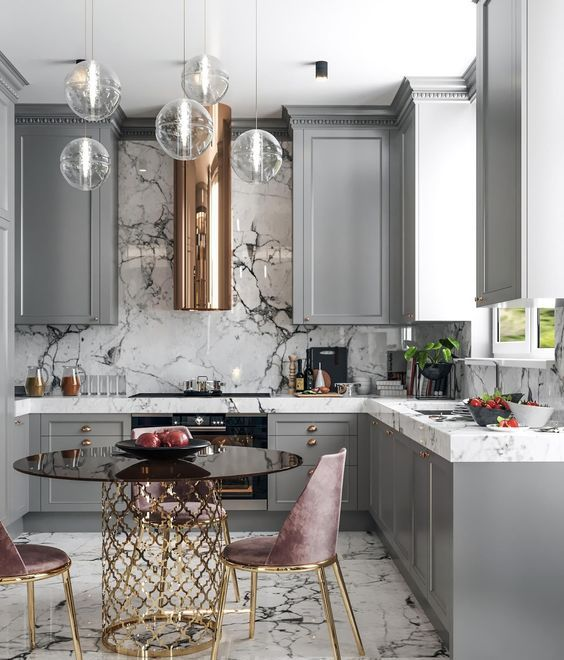 a refined glam ktichen with grey cabinets, white marble coutnertops and a backsplash, a glass table on a gold base, dusty pink chairs and pendant lamps
