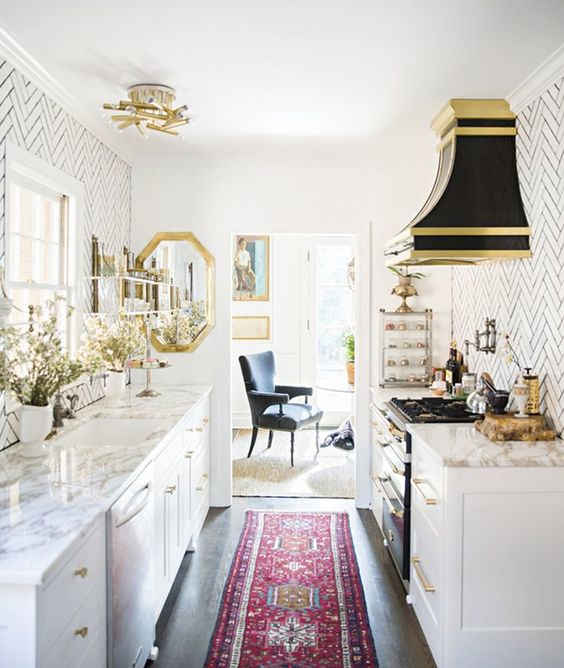 a retro glam kitchen with white cabinets, white marble countertops and a white tile backsplash, a black hood and gold touches