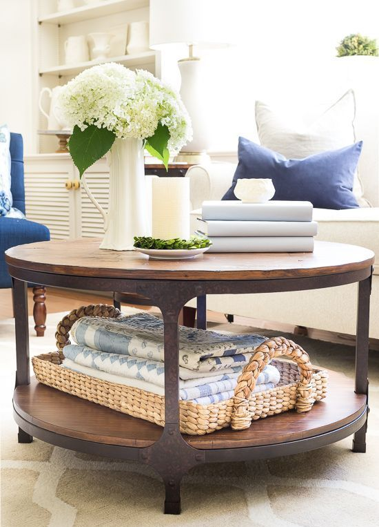 a rustic coffee table with a woven tray with towels, a stack of books, a vase with white blooms, a candle and greenery