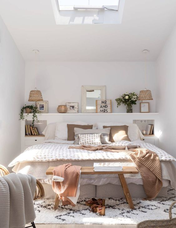 a shelf, a skylight and a neutral color scheme make the bedroom look bigger and more welcoming