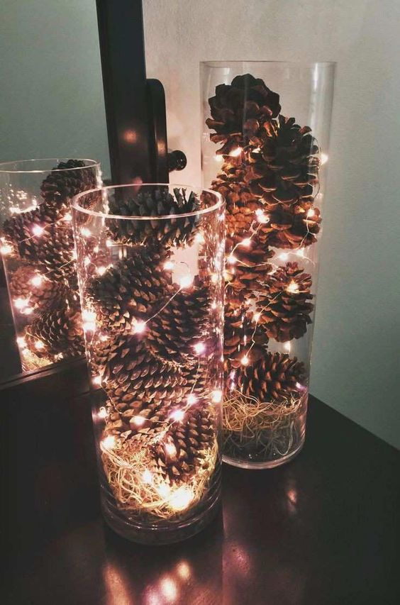 a simple modern fall centerpiece of clear vases with pinecones, hay and lights will fit any space