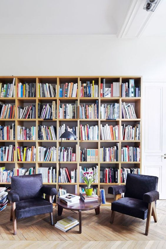 a simple modern library with a large bookcase and black leather chairs plus a side table and a lamp