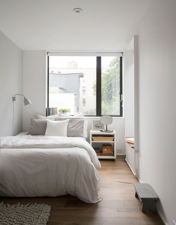 a small bedroom done in neutrals, with a large window over the bed is filled with natural light and looks bigger