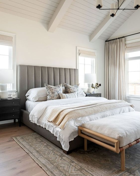 a small bedroom made larger with an extended headboard and with a neutral color scheme