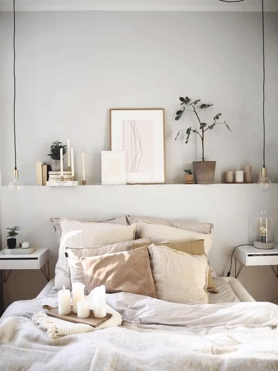 a small bedroom with a built-in shelf over the bed that visually widens the room, a neutral color scheme makes it bigger