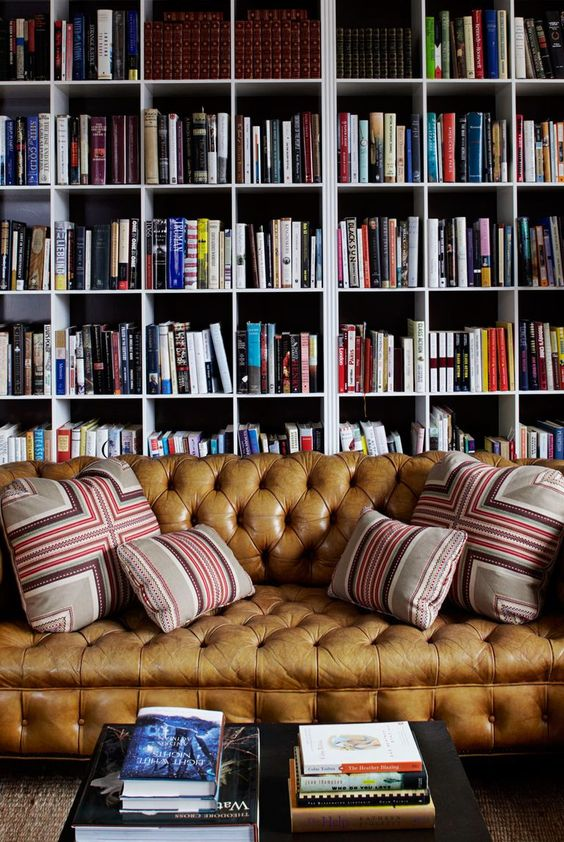 a stylish bookcase that takes the whole wall and a brown leather sofa plus a simple coffee table