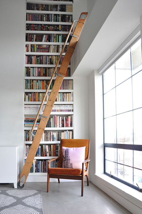 a stylish modern library nook with a double height bookcase, a staircase and a comfy chair in rust