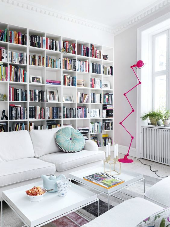 a stylish modern library with a large built in bookcase, white furniture and a whimsy hot pink floor lamp
