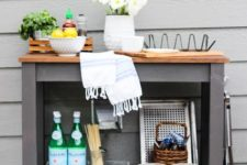 a stylish outdoor bar or grill cart made of an IKEA Forhoja cart painted graphite grey and with a wooden countertop
