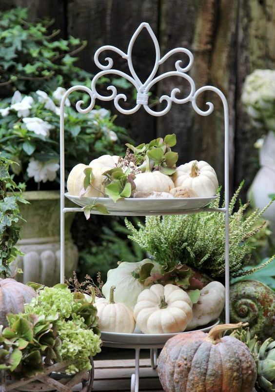 a tiered stand with natural pumpkins and greenery is a perfect farmhouse decoration for the fall