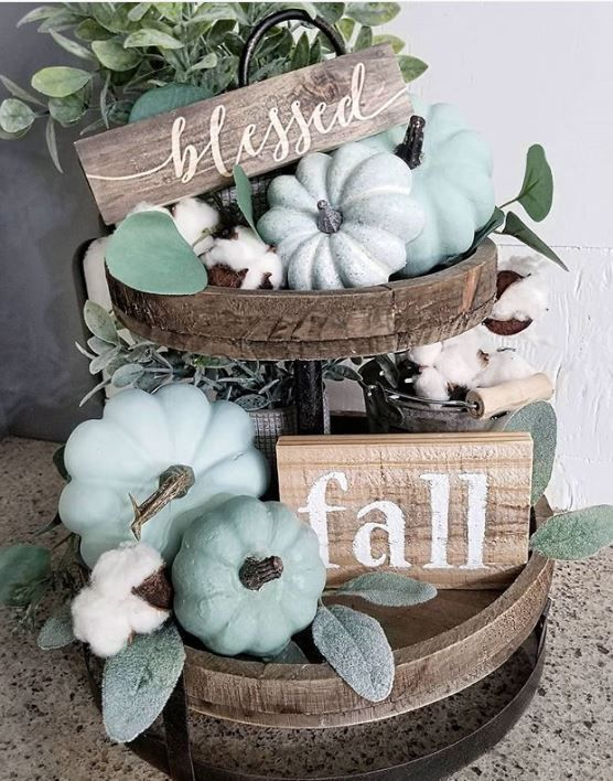 a tiered wooden stand with milky paint and green pumpkins, cotton, wooden signs and greenery as a chic fall centerpiece