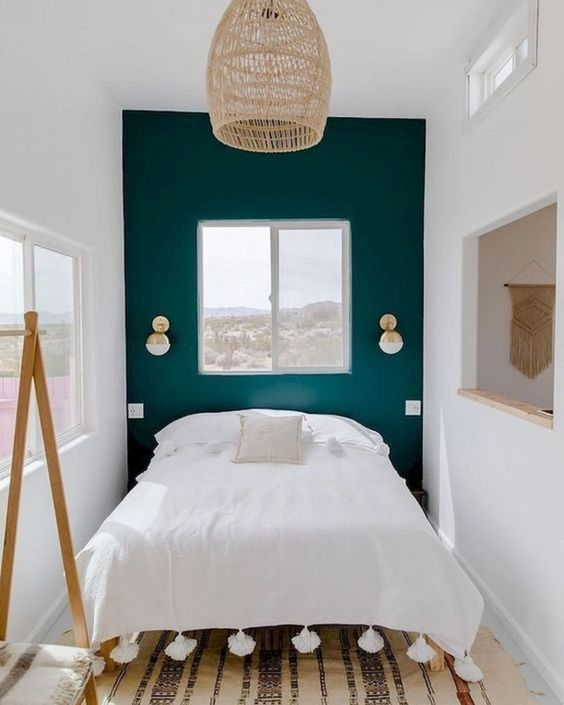 a tiny bedroom enlargened with a neutral color scheme, a mirror and several windows and feels welcoming