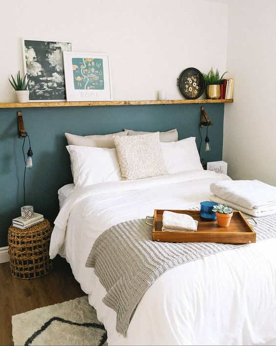 a tiny bedroom made large with a ledge that widens it and a neutral color scheme that makes it visually bigger