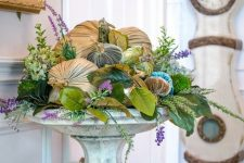 a vintage stone stand with faux greenery and leaves, blooms and velvet pumpkins for timeless fall decor
