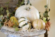 a vintage urn with hay, natural pumpkins and gourds and leaves is a cool centerpiece for the fall