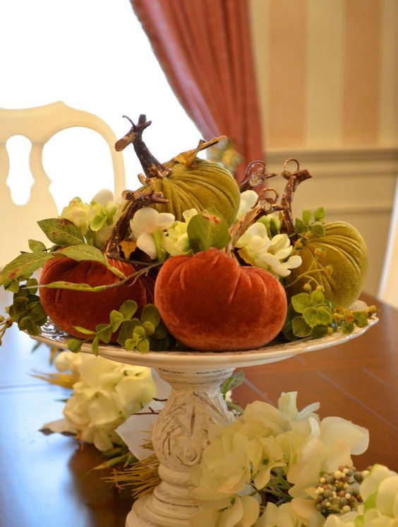 a vintage white stand with bright velvet pumpkins, blooms and leaves is a chic vintage rustic centerpiece