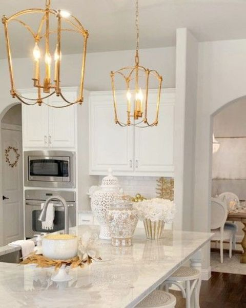 a white glam kitchen with white marble countertops, gold cage pendant lamps and neutral fixtures