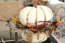 a white painted pumpkin with twigs and faux berries placed in a vintage urn as a stand for a shabby chic touch