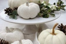 a white porcelain stand with greenery, berries, pinecones, natural and crochet white pumpkins