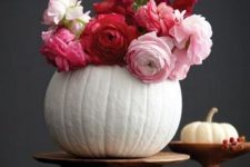 a white pumpkin on a wooden stand with red, fuchsia and pink blooms as a chic and bright fall centerpiece