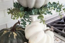 a white stand with eucalyptus and a chalk paint pumpkin plus more pumpkins under it for a rustic feel