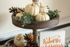 a wooden tiered stand with natural pumpkins, pinecones, eucalyptus and a mini sign is a cool fall decoration