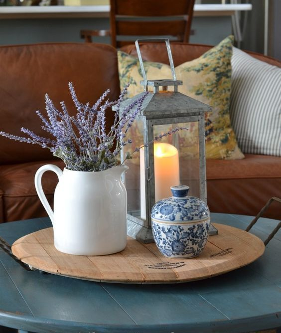 a wooden tray with a vintage candle lantern, a white jug with lavender and a blue patterned sugar pot for small stuff