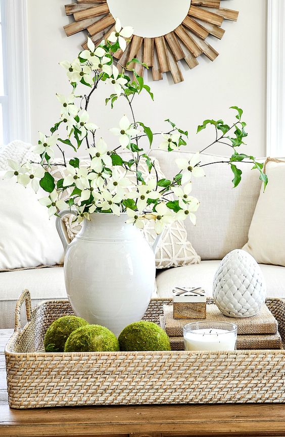 a woven tray with moss balls, a stack of books, a candle, a porcelain egg and a white jug with fresh blooms and greenery