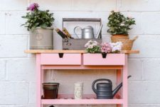 an IKEA Forhoja cart done in millenial pink used for planting and for gardening is a very cute piece