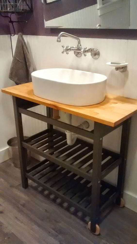 an IKEA Forhoja cart hacked with black paint and with a butcherblock countertop to make a cool rustic vanity
