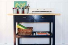 an IKEA Forhoja cart hacked with black paint and with a wooden countertop used as a craft or art cart at home