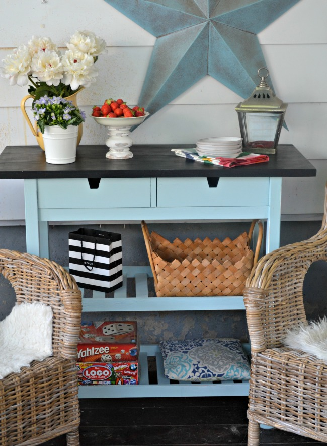 an IKEA Forhoja cart hacked with blue paint and with a chalkboard countertop is used for storage in the kitchen