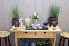 an IKEA Forhoja cart used as a storage piece for outdoors and an outdoor bar with potted greenery and soem lemonade
