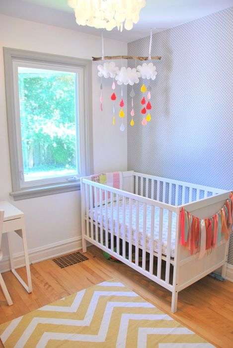 an airy and bright nursery with an IKEA Sundvik crib, colorful touches and decor and simple white furniture