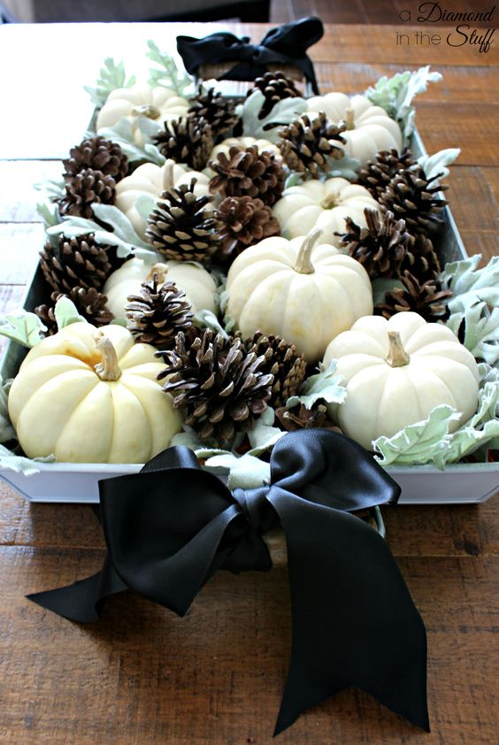 an elegant fall centerpiece of pale greenery, white pumpkins, pinecones and black silk bows