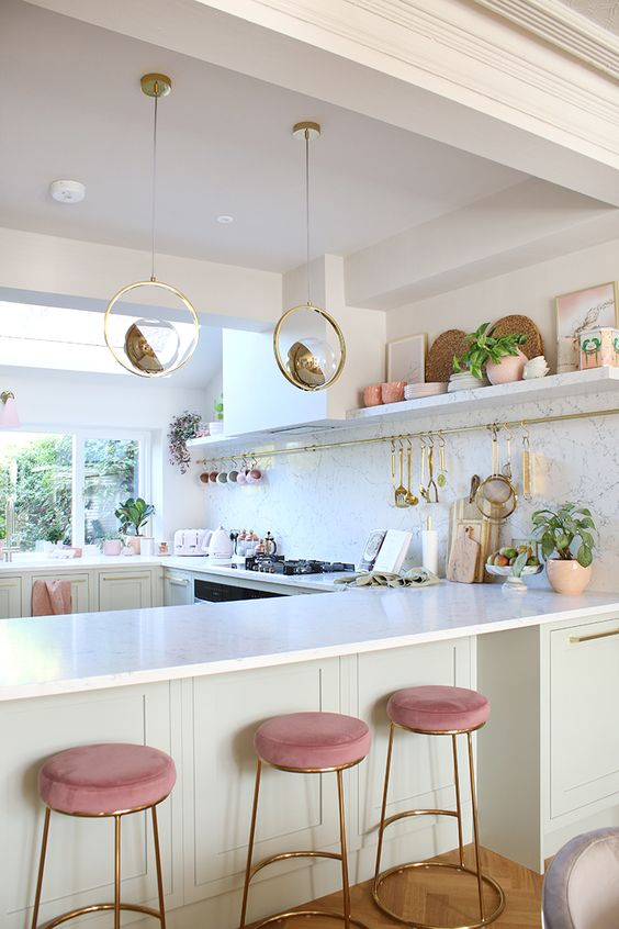 an off-white glam kitchen with white marble countertops and a backsplash, unique pendant sphere lamps, pink stools