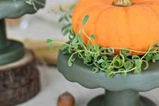 an orange pumpkin with greenery placed on a black stand is a bold and modern fall centerpiece