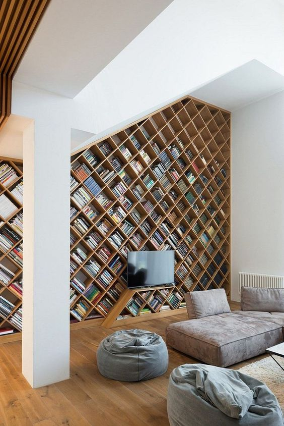 an ultra modern home library with a bookcase with a geometric design plus contemporary furniture in greys