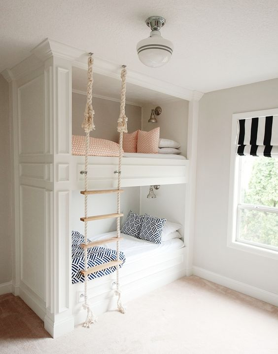 built-in bunk beds with a rope ladder hanging from the ceiling make up a cozy and cute space for sleeping