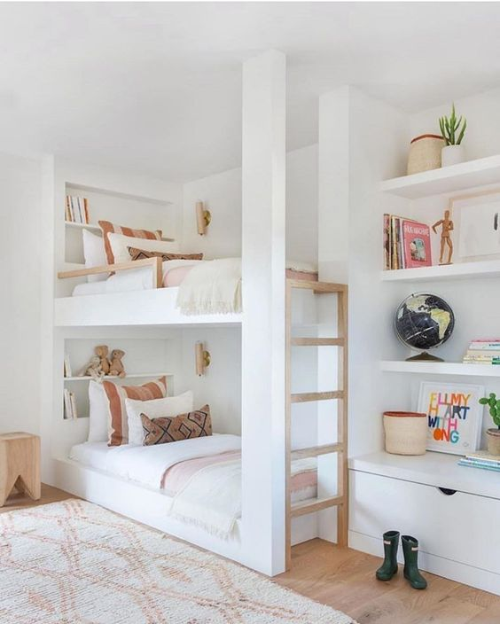 built-in bunk beds with built-in shelves and a ladder byt their side plus small and elegant wall lamps
