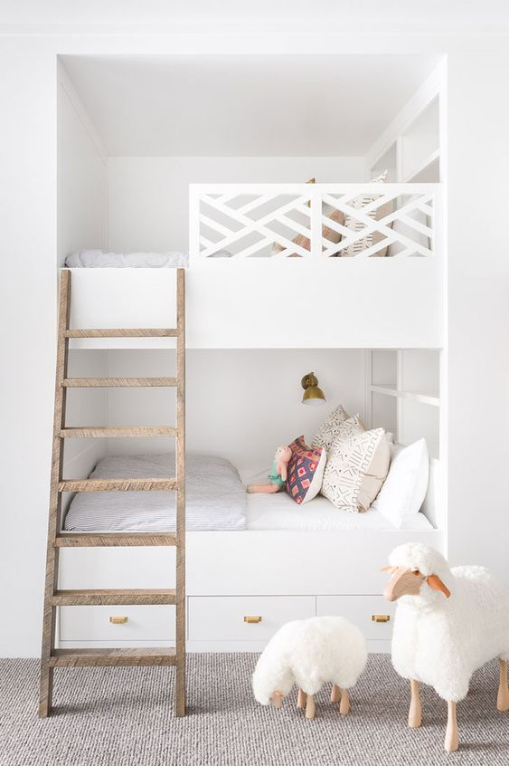 built-in white bunk beds with a wooden ladder, catchy railing, wall lamps and storage drawers in the lower bed