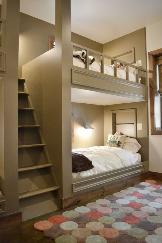 cozy grey bunk beds with a large ladder and wall lamps to make readin there comfortable