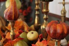 faux pumpkins and pearls on metallic stands, with faux leaves and veggies under them for a chic fall arrangement