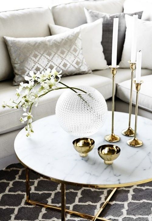 gold bowls, candles in gold tall candleholders and a glass bubble vase with fresh white blooms