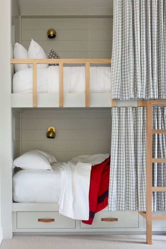 grey bunk beds with a ladder, storage drawers and wall lamps plus gingham curtains to keep privacy
